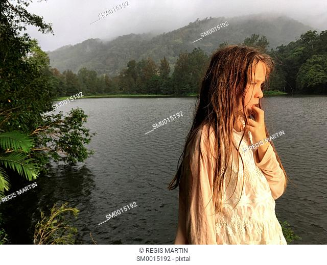 Young pensive girl along the bank of Lake Placid in North Queensland, near the city of Cairns, in Australia