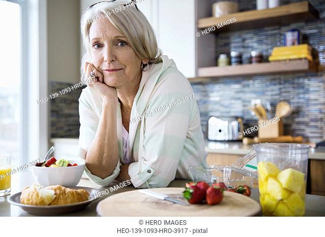 Portrait of woman eating breakfast in kitchen