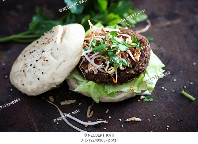 A 'gua bao' bun with a vegan bean burger, mung bean sprouts, fried onions and lettuce (vegan)
