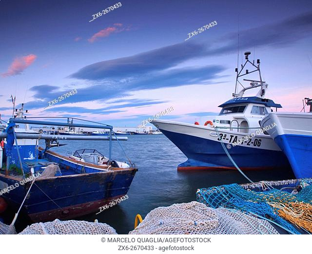 Trawl fishing boats moored at Sant Carles de la Rapita harbour at dusk. Ebro River Delta Natural Park, Tarragona province, Catalonia, Spain