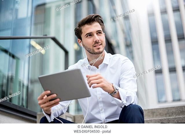 Smiling businessman sitting on stairs with earbuds and tablet