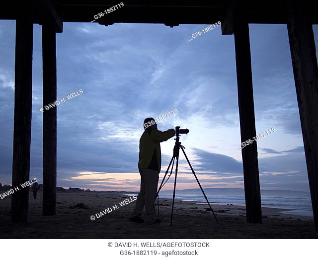 Photographer under the pier and on the beach at sunrise in Pismo Beach, California