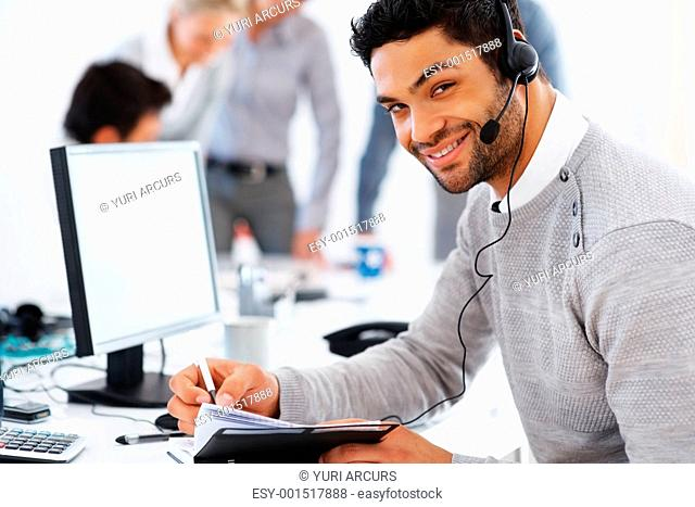 Happy customer care executive noting something in diary with colleagues in background