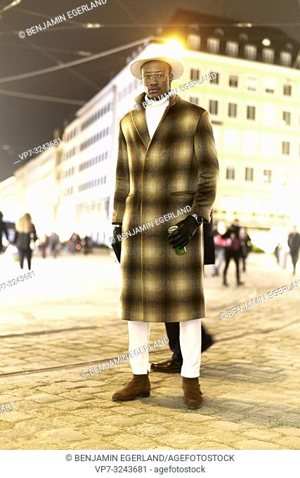 fashionable blogger man standing at street at night, wearing stylish chequered coat, men's winter fashion, Munich, Germany