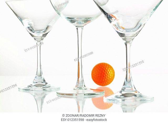 Three glasses of champagne and golf equipments