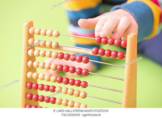 Child hand counting on abacus. Concept of childhood learning, mathematics and early education