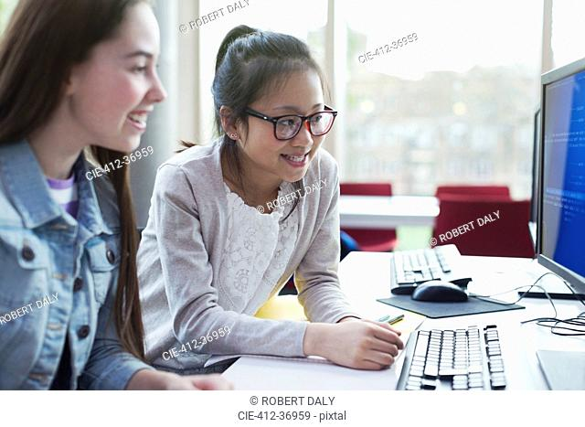 Girl students researching at computer in library