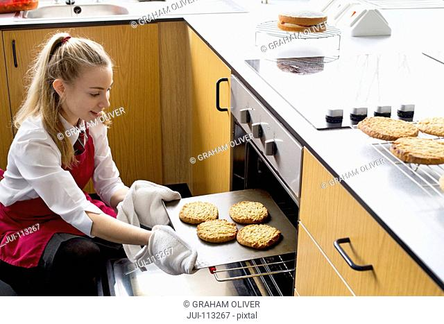 High school student removing baked cookies from oven in home economics class