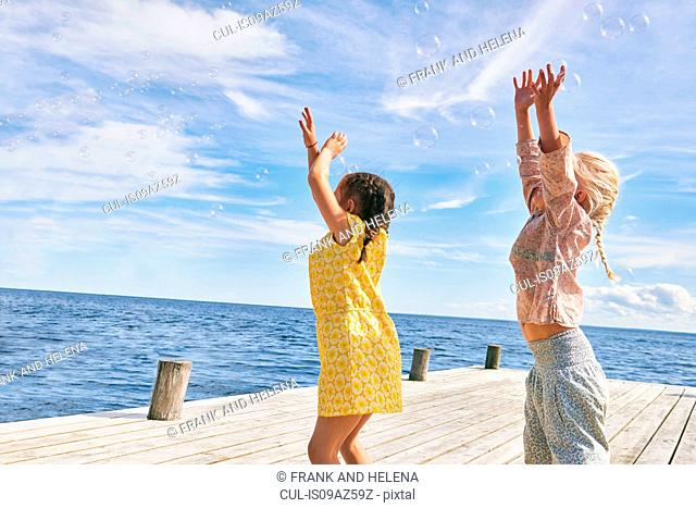 Two young friends playing on wooden pier, reaching for bubbles