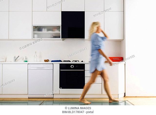 Woman walking in modern kitchen