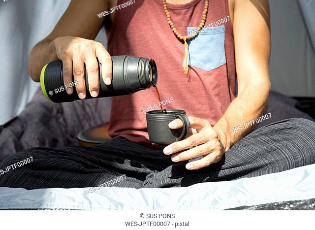 Man sitting in tent pouring coffee into a cup, partial view