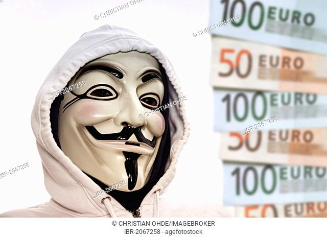 Man wearing the Guy Fawkes mask used by the Occupy movement beside euro banknotes, protesting against the power of banks