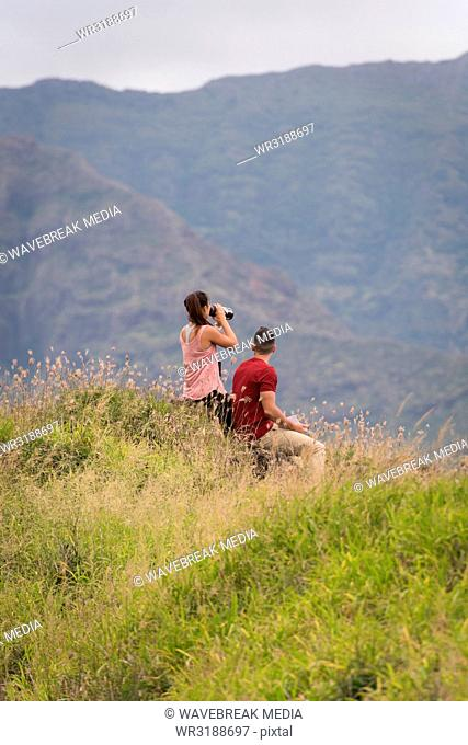 Couple looking through binoculars in countryside