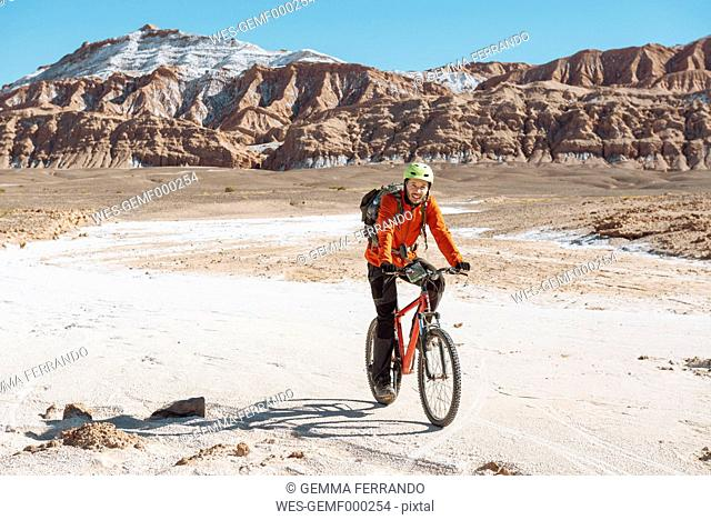 Chile, Man ridding a mountain bike through the Valle de la Muerte, Atacama Desert