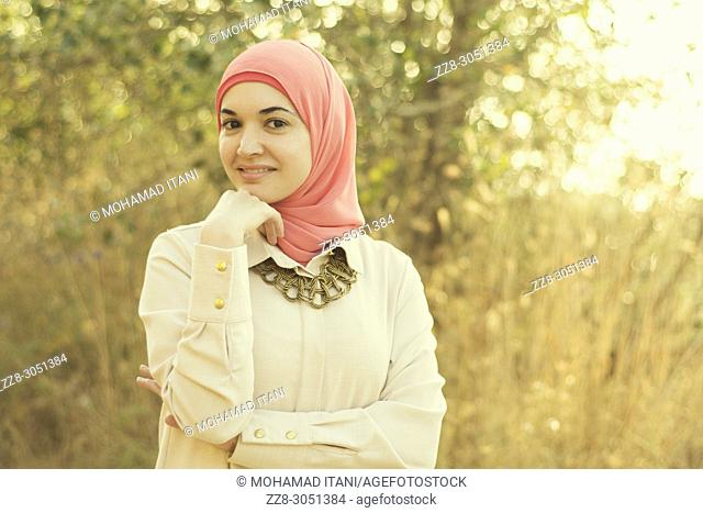 Beautiful Muslim woman hand touching chin smiling outdoors