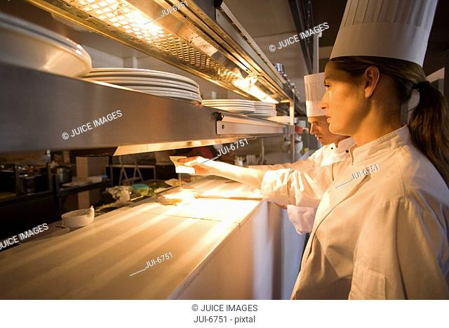 Male and female chefs checking orders at order counter in commercial kitchen, side view