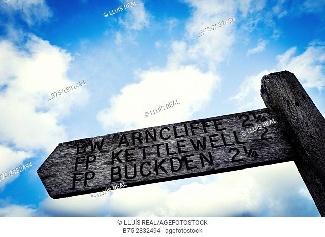 Wooden signpost in a trail. Arnclife, Kettlewell, Buckden. Con el cielo azul y nubes Skipton, North Yorkshire, England, UK