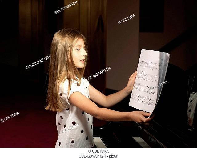Girl choosing sheet music for piano