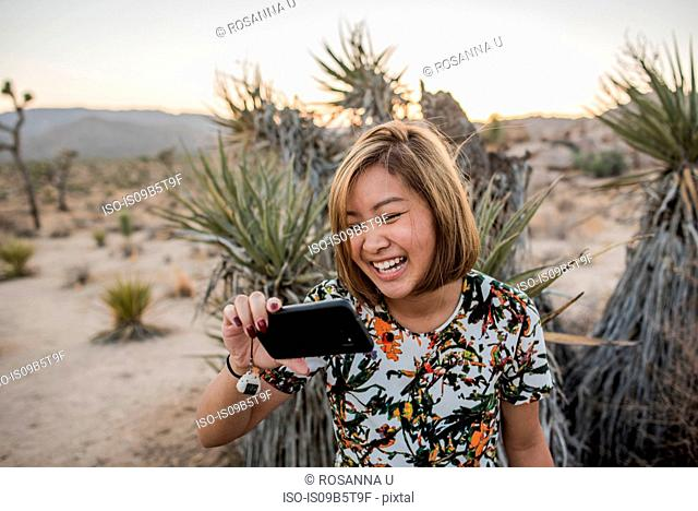 Young woman taking smartphone selfie in Joshua Tree National Park at dusk, California, USA