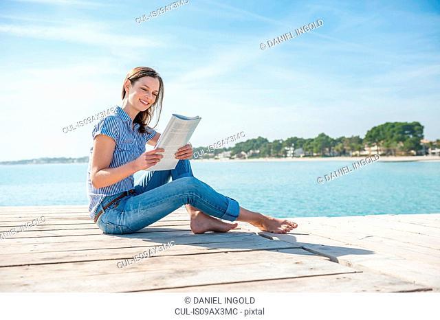 Mid adult woman sitting on pier, reading magazine