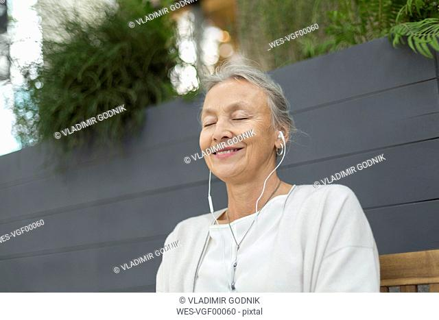 Smiling senior woman with closed eyes wearing earphones outdoors