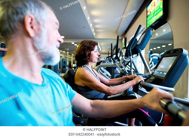 Beautiful fit senior couple in sports clothing in gym doing cardio workout, exercising on recumbent bicycle. Sport fitness and healthy lifestyle concept
