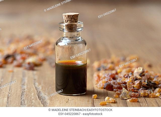 A bottle of essential oil with myrrh resin crystals