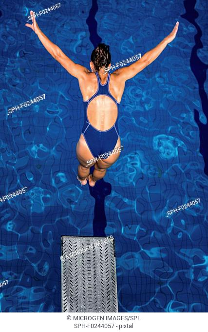 Woman diving into pool from springboard