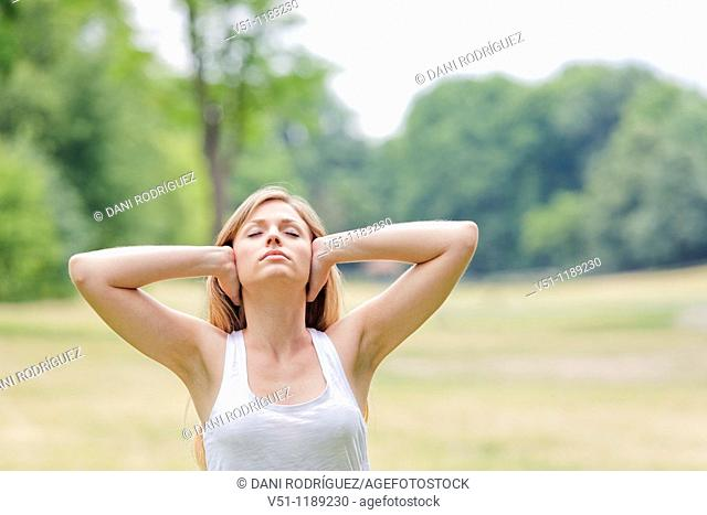 Portrait of a blonde woman covering her ears in the park