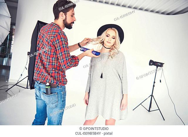 Male photographer adjusting female model's hair on studio white background