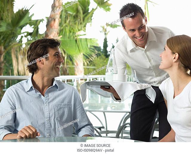Waiter serving a couple