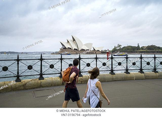 Two people taking in the view of the Sydney Opera House whilst walking along promenade, Sydney, New South Wales, Australia