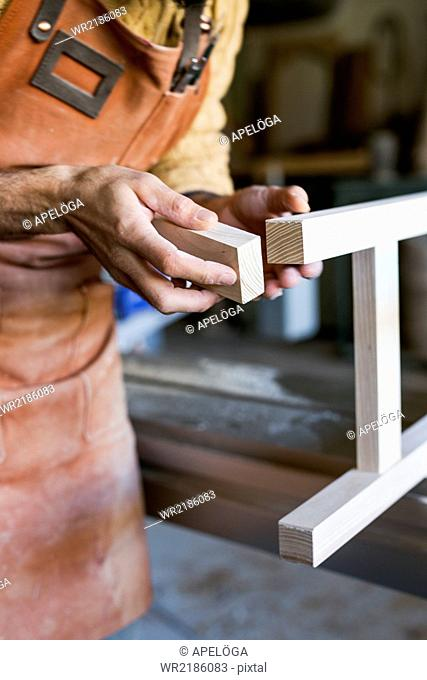 Midsection of carpenter smoothing wood in workshop