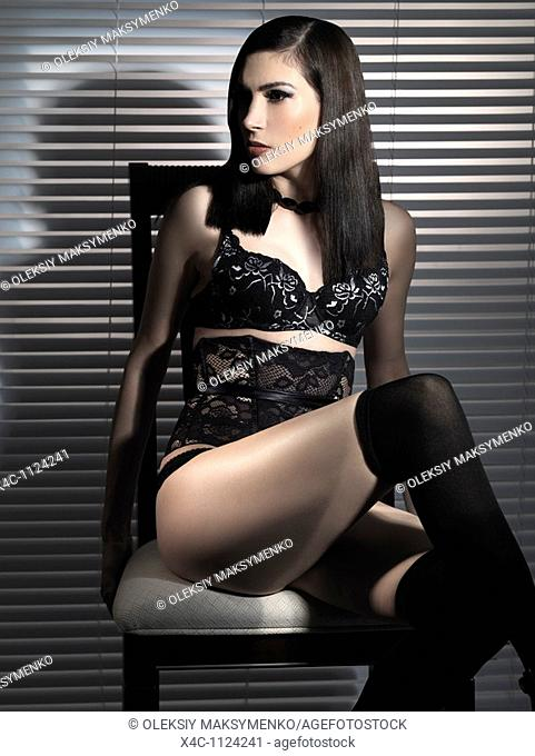 Beautiful young woman in black sexy lingerie sitting on a chair
