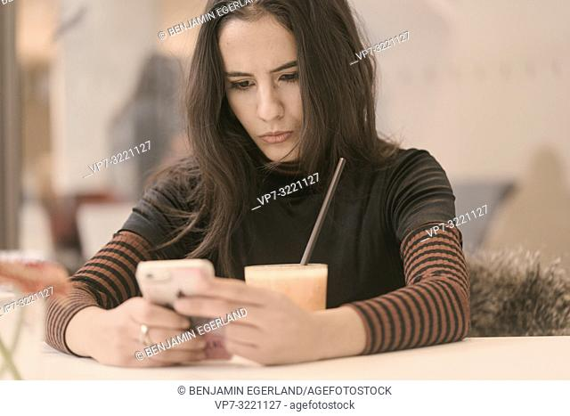 portrait of focused woman using phone while taking a break with healthy juice glass at table in café, curling lips, pout, in Munich, Germany