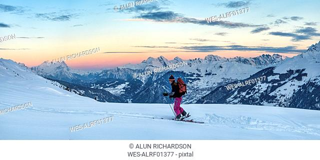 Switzerland, Bagnes, Cabane Marcel Brunet, Mont Rogneux, woman ski touring in the mountains at dusk