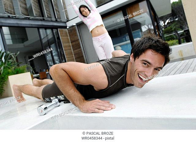Portrait of a mid adult man practicing push-ups with a mid adult woman exercising behind him