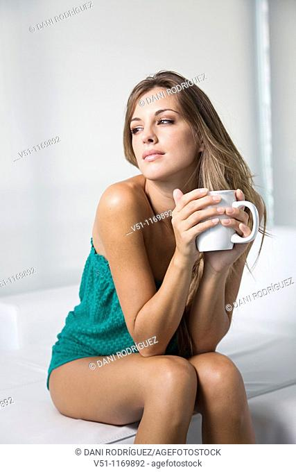 Beatiful pensive blonde woman enjoying a drink at home