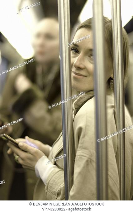 stylish woman holding phone in public transport, in Paris, France