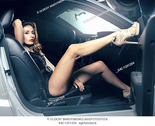 Sexy young woman with beautiful long legs sitting in a luxury car  High fashion photo