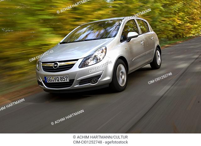Opel Corsa 1.2 Edition, model year 2006-, silver, driving, diagonal from the front, frontal view, country road