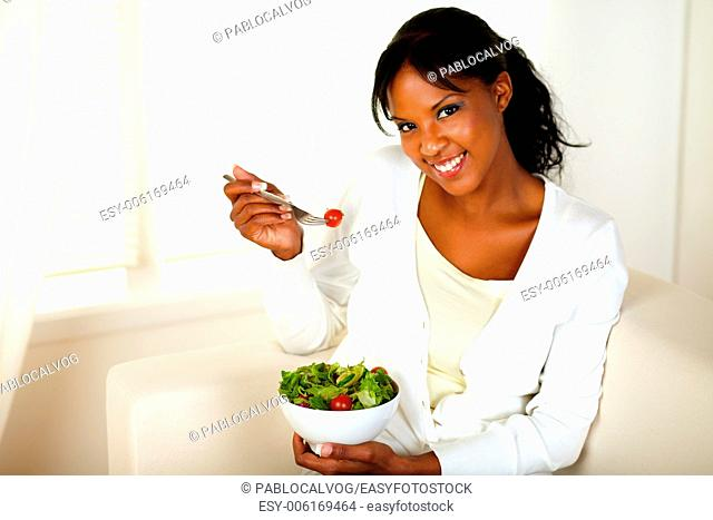 Portrait of a pretty and smiling girl eating a salad and looking at you at home indoor