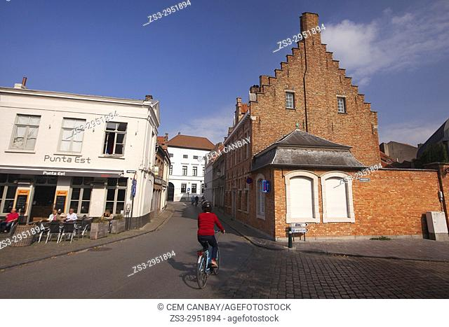 Woman riding on a bike in front of the traditional buildings at the city center, Bruges, West Flanders, Belgium, Europe