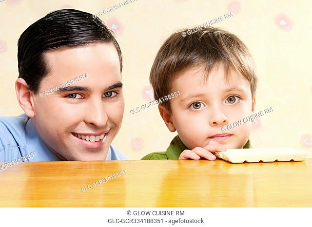 Portrait of a man with his son holding a chocolate bar