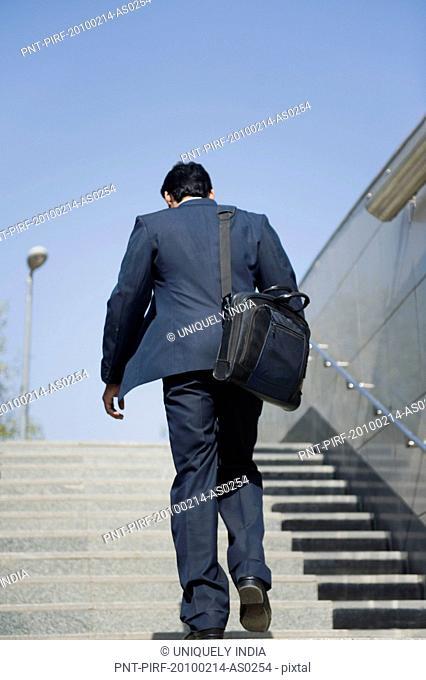 Businessman moving up stairs of subway, Gurgaon, Haryana, India