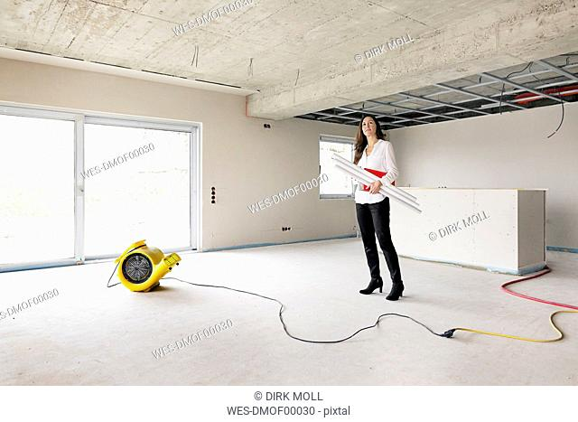 Woman in empty apartment looking around