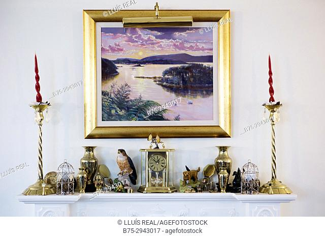Piece of furniture with different objects: two candlesticks, clock, porcelain objects and a picture hanging on the wall in a house. London, England