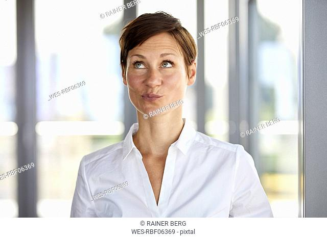 Portrait of businesswoman in office pouting looking up