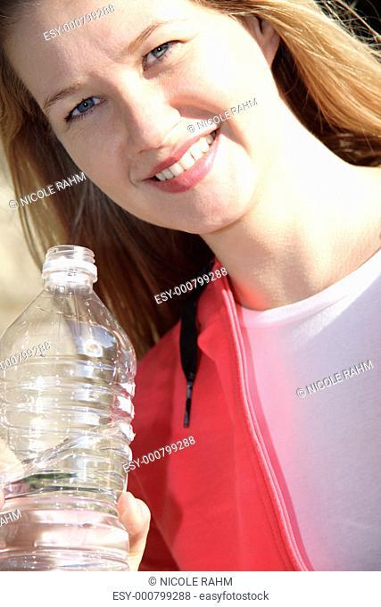 Female jogger holding water bottle, portrait