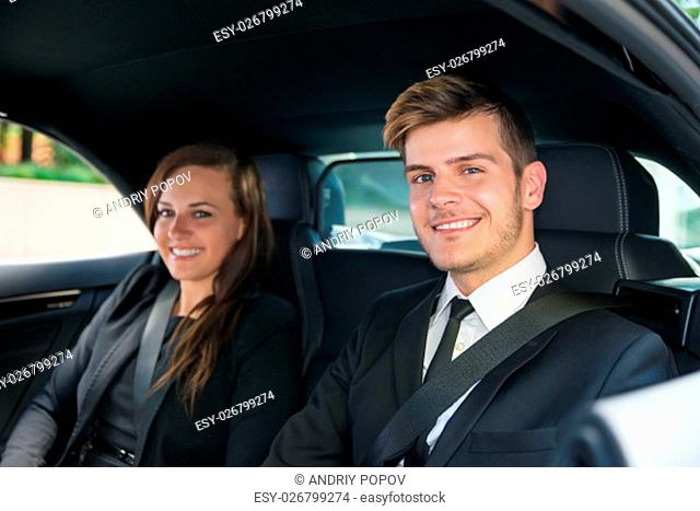 Portrait Of Smiling Businessman And Business Woman Sitting Inside The Car